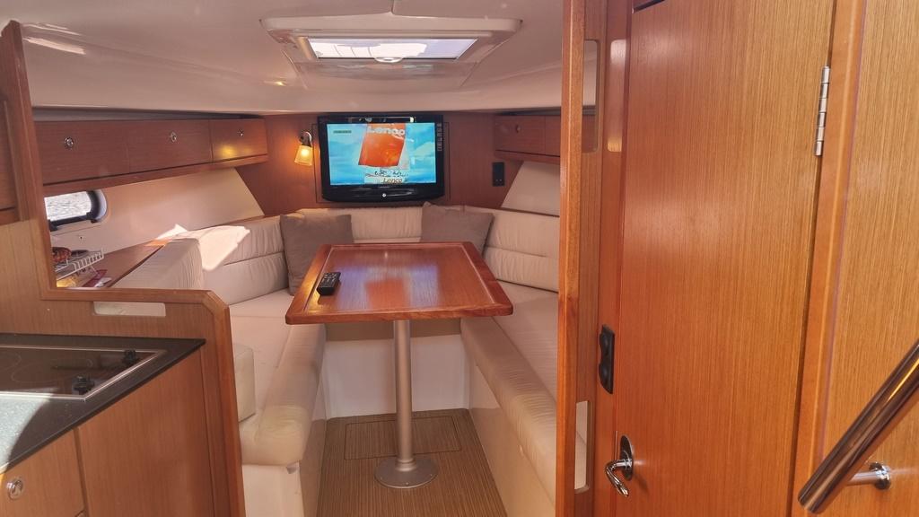 Interieur cabin bavaria 28 avec tv, boiserie acajou et sol chêne clair