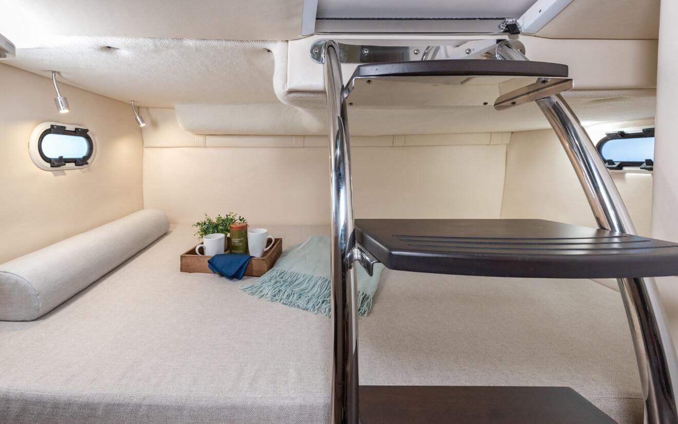Intérieur mid cabin du Regal 26 avec couchage double, deux hublots et décoration sur le lit